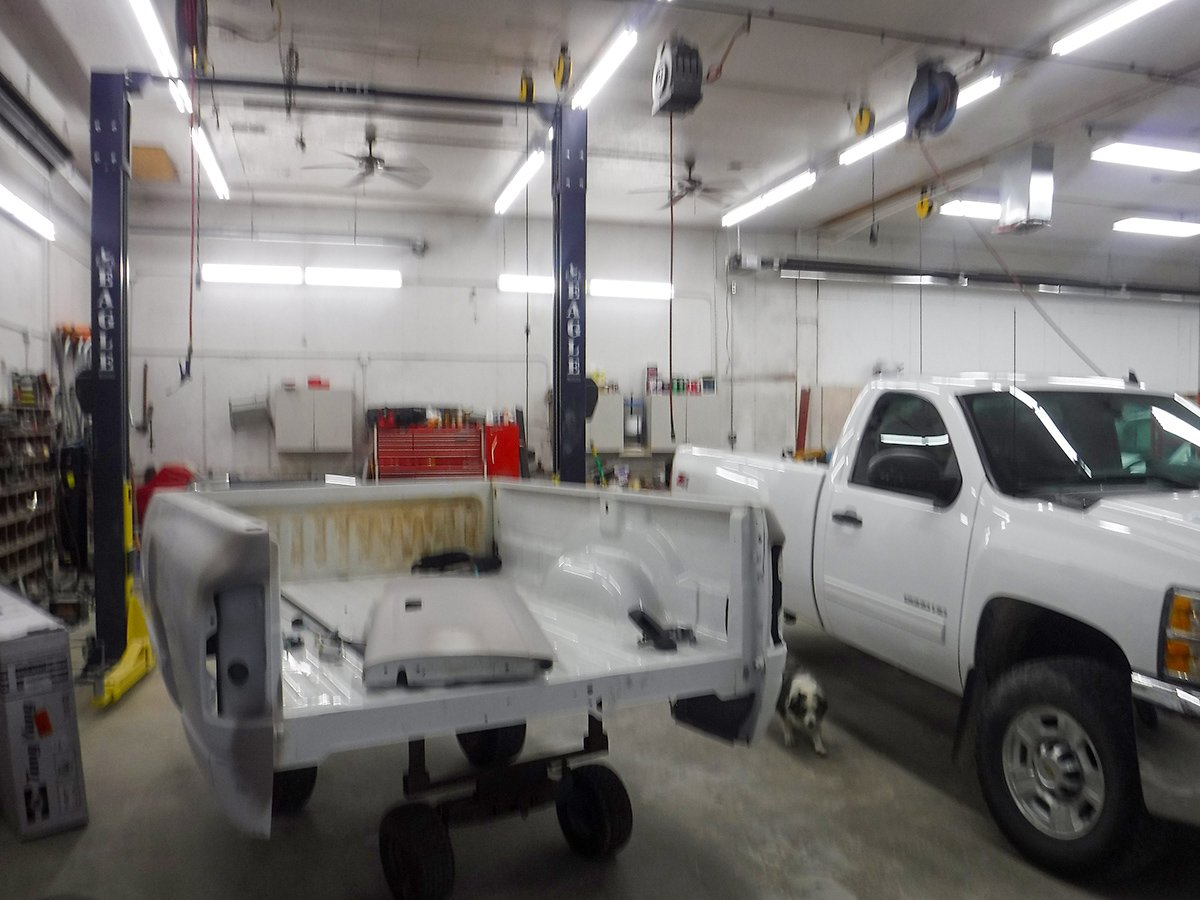 Interior of Schmidtke Auto Body shop with truck bed being worked on
