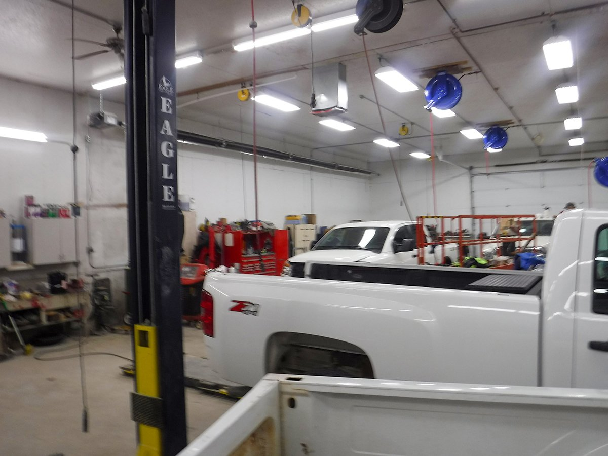 Interior of Schmidtke Auto Body shop with two trucks